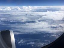 Die Draufsicht von Wolken und von Himmel von einem Flugzeugfenster Lizenzfreies Stockbild