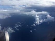 Die Draufsicht von Wolken und von Himmel von einem Flugzeugfenster Stockfotos