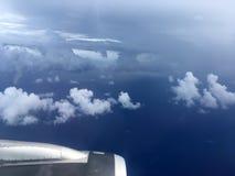 Die Draufsicht von Wolken und von Himmel von einem Flugzeugfenster Stockbilder