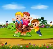 Die drei Kinder spielen auf der großen Schildkröte im Wald lizenzfreie abbildung