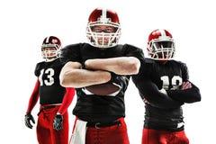 Die drei Spieler des amerikanischen Fußballs, die mit Ball auf weißem Hintergrund aufwerfen Stockfotografie