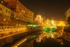 Die dreifache Brücke über dem Ljubljanica-Fluss im Stadtzentrum von Ljubljana und von Franziskanerkirche - Nachtbild Lizenzfreie Stockfotos