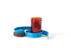 Die Droge oder die Pillen in der roten Flasche mit blauem messendem Band auf lokalisiert Lizenzfreies Stockbild