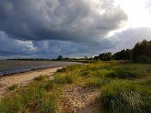 Die dunklen Wolken, die mit Regen gefüllt werden, treffen den Sonnenschein, der dem sandigen Strand in Halmstad, Schweden leuchte lizenzfreies stockfoto