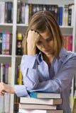 Die durchdachte Frau in der Bibliothek Stockfoto
