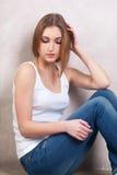 Die durchdachte Frau sitzt auf einem Boden nahe einer weißen Wand Lizenzfreie Stockfotografie