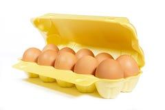 Die Eier des Huhns im Kasten färben Farbe auf weißem Hintergrund gelb Lizenzfreie Stockbilder