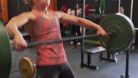 Die Eignungsfrau, die den sauberen Barbell tut - und - stoßen Sie Training in der Turnhalle stock video footage