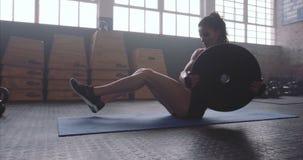 Die Eignungsfrau, die auf Kern ausarbeitet, mischt an crossfit Turnhalle mit stock video