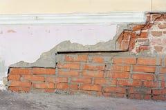 Die eingestürzte Ecke des alten Backsteinhauses wird mit einer frischen Maurerarbeit des roten Backsteins repariert Lizenzfreie Stockfotos
