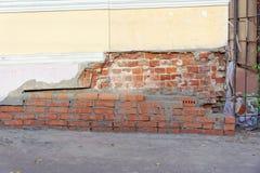 Die eingestürzte Ecke des alten Backsteinhauses wird mit einer frischen Maurerarbeit des roten Backsteins repariert Lizenzfreie Stockbilder