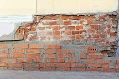 Die eingestürzte Ecke des alten Backsteinhauses wird mit einer frischen Maurerarbeit des roten Backsteins repariert Lizenzfreie Stockfotografie