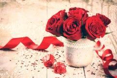 Die Einstellung des Valentinsgrußes mit Blumenstrauß von roten Rosen und von Schokolade Stockfotos