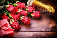 Die Einstellung des Valentinsgrußes mit roten Rosen, Champagner und Geschenk Stockfoto