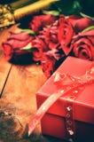 Die Einstellung des Valentinsgrußes mit roten Rosen und Geschenkbox lizenzfreies stockbild