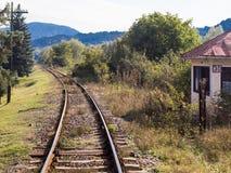 Die Eisenbahn, die durch eine Waldfläche überschreitet und weit weg vom Dorf von Prahova in Rumänien verlässt Stockbilder