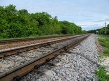 Die Eisenbahn läuft in den Abstand weg und verschwindet im Wald Stockfoto