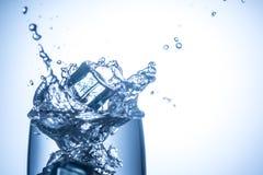 Die Eiswürfel, die in Glas mit Wasser fallen, spritzt nah oben Lizenzfreies Stockbild