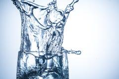 Die Eiswürfel, die in Glas mit Wasser fallen, spritzt nah oben Stockfoto