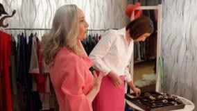 Die elegante ältere Frau versucht auf Ohrringen sprechend mit dem Verkäufer im Speicher vor dem Spiegel stock footage