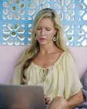 Die elegante blonde Frau, die online arbeitet, entspannte sich mit Laptop-Computer als digitaler Nomade und Social Media Blogger  Lizenzfreies Stockfoto