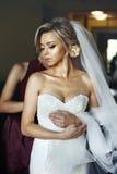 Die elegante Brautjungfer, die schöner blonder Braut hilft, bereiten sich für uns vor Lizenzfreies Stockbild