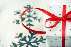 Die elegante Geschenkbox, die in Grey Silver Paper mit Tupfen-rotem Band auf Snowy-Hintergrund mit Schnee eingewickelt wird, blät Stockbild
