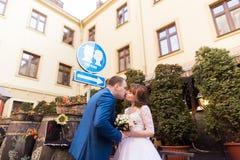 Die eleganten Hochzeitspaare, die unter dem Zeichen küssen, küssen Platz Lizenzfreies Stockfoto