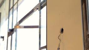Die elektrischen herausgestellten Drähte, die vom Sockel auf eben hervorstehen, deckt c mit Ziegeln stock video footage