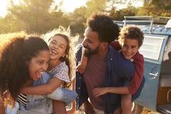 Die Eltern, die ihre Kinder geben, trägt, Taille oben huckepack Lizenzfreie Stockfotografie