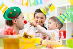 Die Eltern haben Spaß Geburtstag seines Sohns feiernd lizenzfreies stockfoto