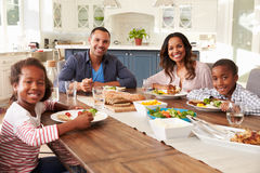 Die Eltern und Kinder, die am Küchentisch essen, schauen zur Kamera Lizenzfreie Stockfotografie