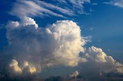 Die enormen weißen Wolken, die über den blauen Himmel sich bewegen, werden durch die Sonne bei Sonnenuntergang belichtet lizenzfreie stockfotografie