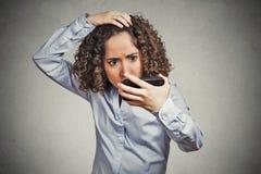 Die entsetzte lustige schauende junge Frau, überrascht ist sie verlierendes Haar Lizenzfreie Stockbilder