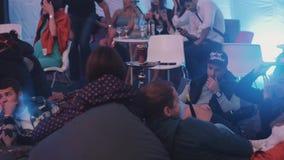 Die entspannenden jungen Leute rauchen Huka und sprechen und lachen das Sitzen auf Bohnentaschen stock video footage