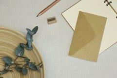 Die eröffneten Notizbuch-, Bleistift-, Bleistiftspitzer-, Umschlag- und Eukalyptusfilialen im Korb lizenzfreies stockbild