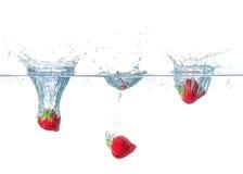 Die Erdbeeren, die in Wasser mit fallen, spritzt stockfotos