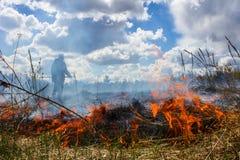 Die Erde brennt, die Feldbrände und der starke Rauch Der Mann im Rauche Hintergrund Stockfoto