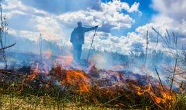Die Erde brennt, die Feldbrände und der starke Rauch Der Mann im Rauche Hintergrund Lizenzfreies Stockfoto