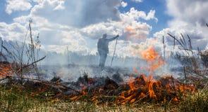 Die Erde brennt, die Feldbrände und der starke Rauch Der Mann im Rauche Hintergrund Lizenzfreies Stockbild