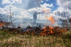 Die Erde brennt, die Feldbrände und der starke Rauch Der Mann im Rauche Hintergrund Lizenzfreie Stockfotografie