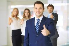 Die erfolgreichen jungen Geschäftsleute, die Daumen zeigen, up Zeichen Lizenzfreie Stockfotografie