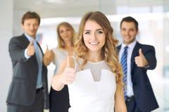 Die erfolgreichen jungen Geschäftsleute, die Daumen zeigen, up Zeichen Stockfoto