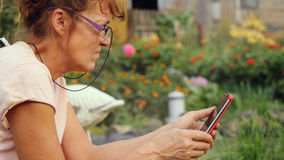 Die ernste schöne reife Frau, die herein in den Gläsern gealtert wird, sitzt im Garten auf dem Schwingengebrauch einen Handy Stockfoto