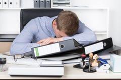 Die erschöpften Junge bemannen liegen auf dem Schreibtisch im Büro Stockfotos