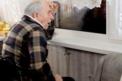 Die erschrockenen älteren Personen bemannen das Aufpassen durch ein Fenster Stockbilder