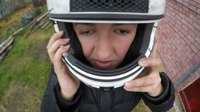 Die erwachsene Frau, die auf ihren Motorrad Sturzhelm, glückliches Gesicht sich setzt, Extrem wagt Adrenaline stock video