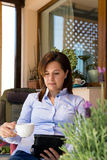 Die erwachsene Frau, die auf digitaler Tablette gelesen wird und entspannen sich auf dem Terrasse drin lizenzfreies stockbild
