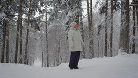 Die erwachsene Frau im Winterholz Der Pensionär genießt den Rest, den das Alter in einem Skianzug Schönheit des Vorderteils bewun stock video