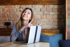 Die europäische blonde weibliche Person, die Gesichter mit den Zeigefingern macht, nähern sich Laptop Lizenzfreie Stockbilder